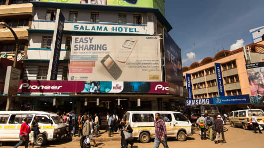 Pedestrians pass an advertisement for the Nokia Asha 205 smartphone in Nairobi, Kenya, on April 17, 2013.