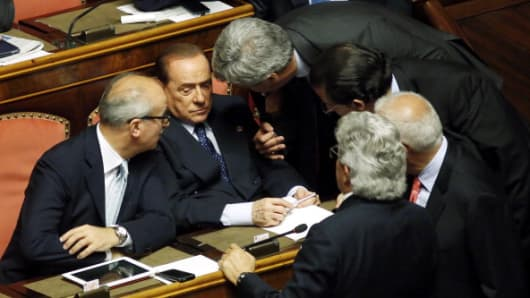 Silvio Berlusconi, Italy's former prime minister, speaks with colleagues during a parliamentary session inside the Senate