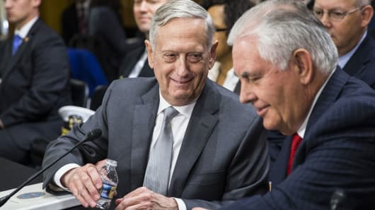Secretary of Defense James Mattis (L) pours then-Secretary of State Rex Tillerson (R) a glass of water before a Senate Foreign Relations hearing in Washington, October 30, 2017.