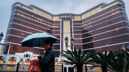 A pedestrian with an umbrella walks in front of the Wynn Palace casino resort, operated by Wynn Resorts Ltd., in Macau, China, Jan. 31, 2018.