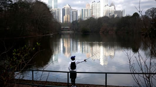 A resident casts his fishing rod against the midtown skyline in Piedmont Park in Atlanta.