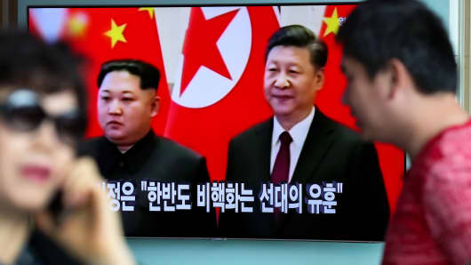 People walk past a television screen showing a news broadcast, featuring North Korean Leader Kim Jong Un during a meeting with with China's president Xi Jinping, at Seoul Station in Seoul, South Korea, on Wednesday, March 28, 2018.