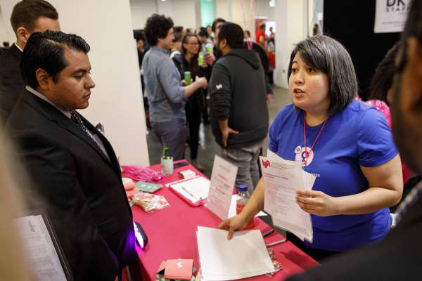 A Lyft representative speaks with job seekers during the TechFair LA career fair in Los Angeles, March 8, 2018.