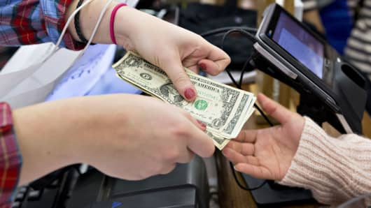 A cashier returns cash to a customer at a Vineyard Vines store at the Fashion Outlets of Chicago.