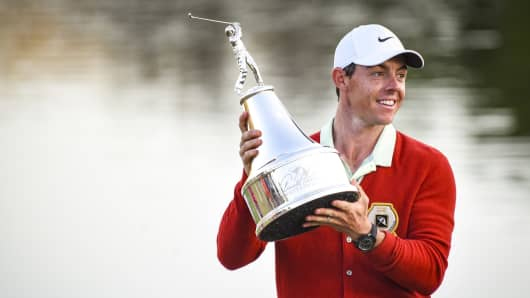 Rory McIlroy of Northern Ireland smiles and holds the tournament trophy while wearing a replica Arnold Palmer red cardigan following his three stroke victory on the 18th hole green in the final round of the Arnold Palmer Invitational presented by MasterCard at Bay Hill Club and Lodge on March 18, 2018 in Orlando, Florida.