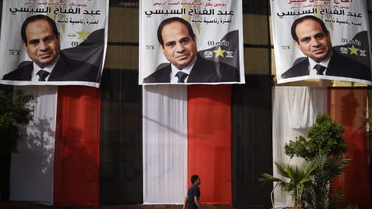 An Egyptian youth walks past a polling station in the capital Cairo's western Giza district on March 25, 2018 ahead of the vote scheduled to begin the following day, decorated on the outside with giant privately-sponsored electoral posters depicting incumbent President Abdel Fattah al-Sisi and giant pieces of cloth stacked together to show the colors of the Egyptian flag.