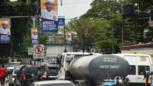 Motorists wait in traffic under banners bearing portraits of Nigerian President Muhammadu Buhari on March 29, 2018, in Lagos, Nigeria.