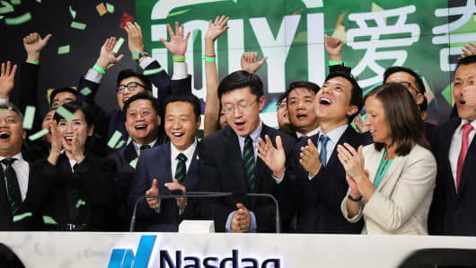 Yu Gong (center), Founder and CEO of China-based iQiyi (IQ), rings the Opening Bell at Nasdaq MarketSite in Times Square with employees and investors in celebration of its initial public offering (IPO) on March 29, 2018 in New York City.
