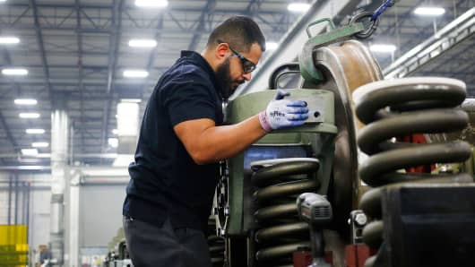 An employee helps install a traction motor onto the truck of a General Electric Evolution Series Tier 4 diesel locomotive at the GE Manufacturing Solutions facility in Fort Worth, Texas.