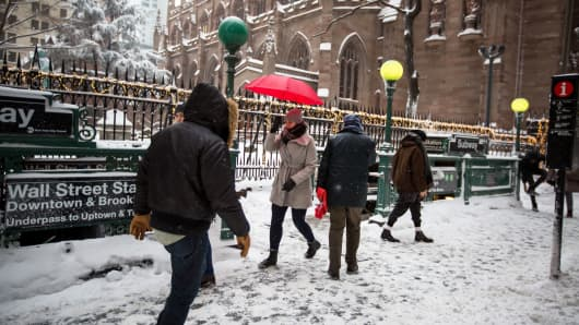 Pedestrians walk in snow past the Wall Street subway station near the New York Stock Exchange.