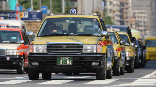 Taxis sit in traffic as they wait for a traffic signal to change at a junction in Tokyo, Japan.