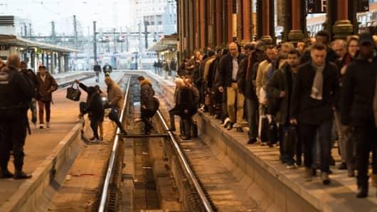 People cross railroad tracks at the Gare de Lyon railway station in Paris on April 3, 2018.