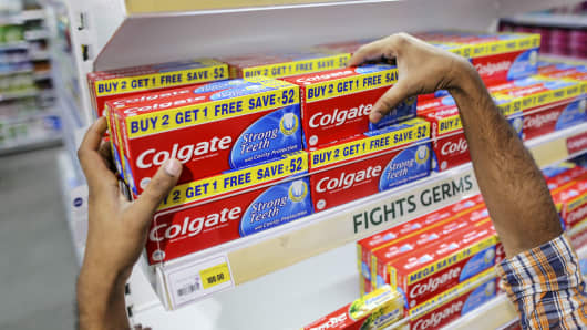An employee arranges Colgate-Palmolive's Colgate brand toothpaste.