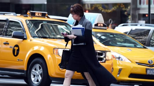 A woman uses her mobile phone while crossing a street in New York.