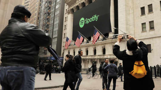 Pedestrians walk past a banner with the Spotify logo on the New York Stock Exchange, April 3, 2018.