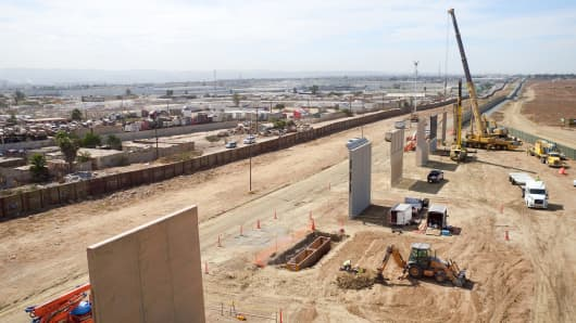 Construction crews prepare a set of border wall prototypes along the U.S. border with Mexico on U.S. Customs and Border Protection property near San Diego, California.