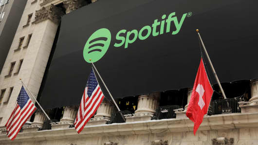 The Spotify logo hangs on the facade of the New York Stock Exchange with U.S. and a Swiss flag as the company lists it's stock with a direct listing in New York, April 3, 2018.