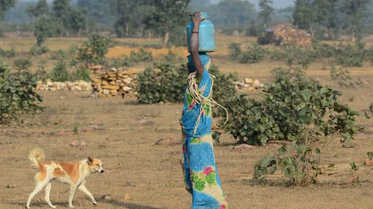 An indian woman carries drinking water in steel and plastic containers, walking towards her temporary shelters in Rataiora Village on December 15, 2016.