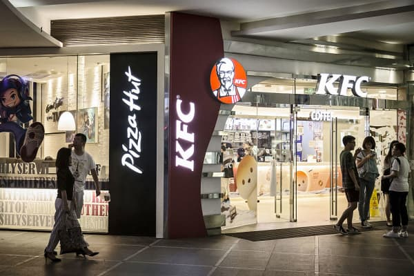 Pedestrians walk past Yum! Brands Inc. Pizza Hut and KFC restaurants in Shanghai, China