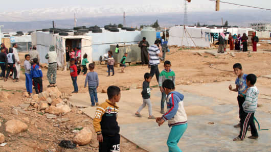 Syrian refugees play at an unofficial refugee camp in Lebanon's Bekaa valley on March 8, 2018.