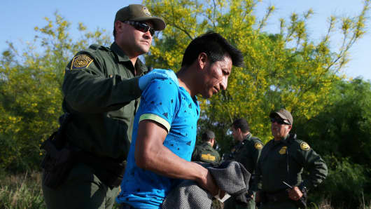 Border patrol agents apprehend an immigrant who illegally crossed the border from Mexico into the U.S. in the Rio Grande Valley sector, near McAllen, Texas, April 2, 2018.