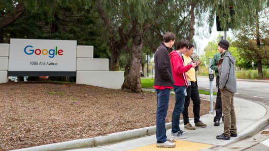 A group of millennial-age technology workers stand near signage for Google at the Googleplex, the Silicon Valley headquarters of search engine and technology company Google Inc, Mountain View, California.