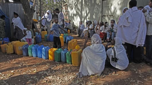 Women queue for water with plastic cans in the outskirts of Addis Ababa, Ethiopia, on May 16, 2013.