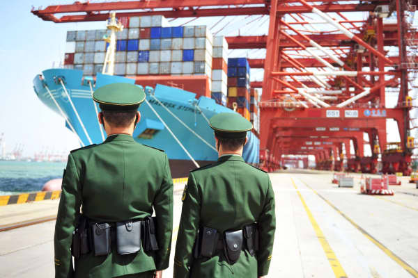 Police officers are seen in front of a cargo ship with containers at a port in Qingdao, Shandong province, China April 6, 2018.