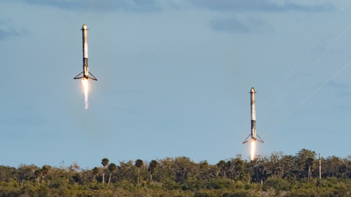 The two side boosters of SpaceX Falcon Heavy return to land after launching only minutes before.