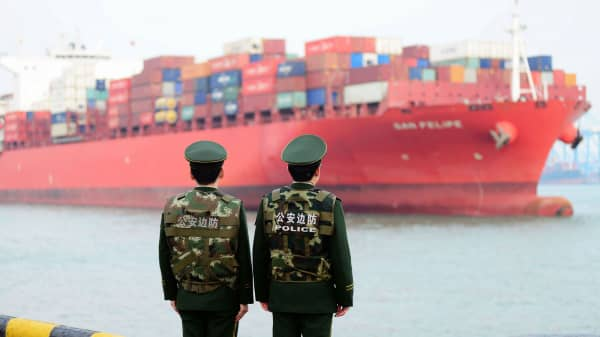 Soldiers wait for a container ship to berth at Qingdao Port on March 8, 2018 in Qingdao, China.