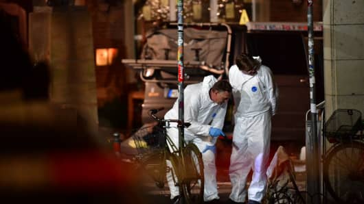 Police officers and forensic scientists stand by a van who has been driven by a suspect into a crowd of people seated outside a pub on April 8, 2018 in Muenster, Germany.