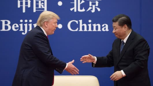 China's President Xi Jinping shakes hands with U.S. President Donald Trump (L) during a business leaders event at the Great Hall of the People in Beijing on Nov. 9, 2017.