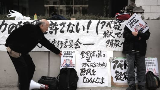 People gathering near the Japan Parliament hold placards against Japanese Prime Minister Shinzo Abe as Yasunori Kagoike, head of the Moritomo Gakuen group, gives sworn testimony in the Diet on March 23, 2017.