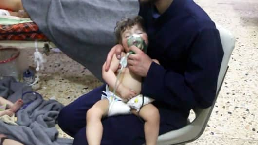 This image made from video released by the Syrian Civil Defense White Helmets, which has been authenticated based on its contents and other AP reporting, shows a medical worker giving toddlers oxygen through respirators following an alleged poison gas attack in the opposition-held town of Douma, in eastern Ghouta, near Damascus, Syria, Sunday, April 8, 2018.