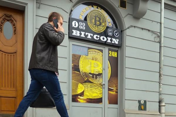 A man passes in front of a Bitcoin exchange shop in Krakow, Poland.