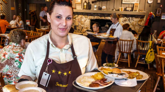 A waitress serving plates of food in a restaurant inside Cracker Barrel Country Store.