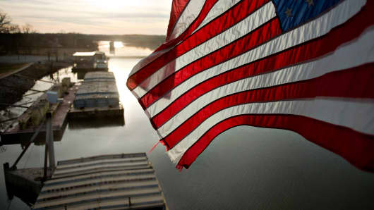 A U.S. flag flies above barges filled with soybeans on the Kaskaskia River, a tributary of the Mississippi River, at Gateway FS in Evansville, Illinois, U.S.