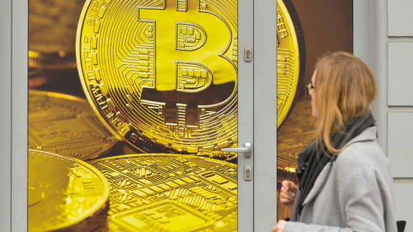A lady passes in front of a Bitcoin exchange shop