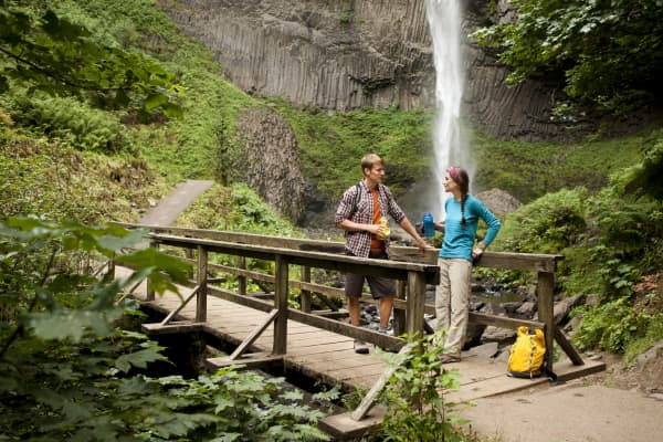 A young couple hiking and exploring the waterfalls in Oregon's Columbia Gorge.