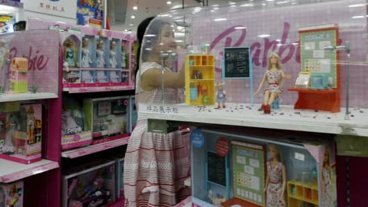 A girl looks at Barbie Dolls at a department store.