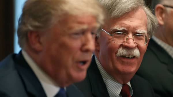National Security Advisor John Bolton (R), listens to U.S. President Donald Trump as he speaks about the FBI raid at lawyer Michael Cohen's office, while receiving a briefing from senior military leaders regarding Syria, in the Cabinet Room, on April 9, 2018 in Washington, DC.