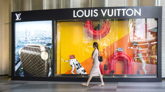 A pedestrian walks past the window display of a Louis Vuitton store, operated by LVMH Moet Hennessy Louis Vuitton SE.