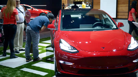 People inspect the Tesla Model 3 as it sits on display at the Los Angeles Auto Show last December.
