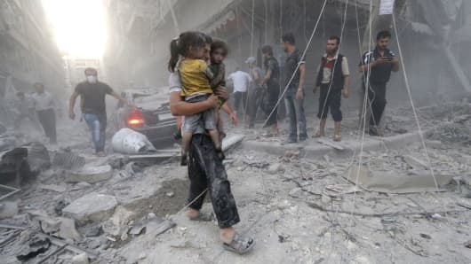 A Syrian man carries two girls covered with dust following a reported air strike by government forces on July 9, 2014 in the northern city of Aleppo.