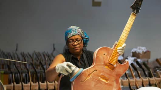 An employee buffing an unfinished electric guitar inside a Gibson factory.