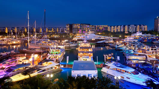 Luxury yachts illuminated at night sit moored in front of residential buildings in the Sentosa Cove during the Singapore Yacht Show in Singapore, on Saturday, April 25, 2014.