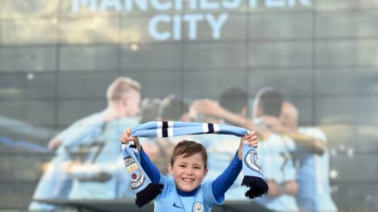 City fan, seven year old Bobby English poses on his father's shoulders as Manchester City supporters gather outside the Etihad Stadium in Manchester, north west England, on April 15, 2018, Manchester City were crowned Premier League champions on Sunday as Manchester United crashed to a shock 1-0 defeat against West Bromwich Albion.
