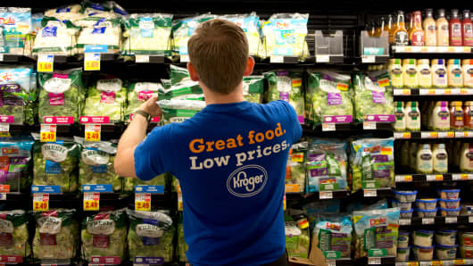 An employee stocks salad mixes in the produce department of a Kroger supermarket in Peoria, Illinois.