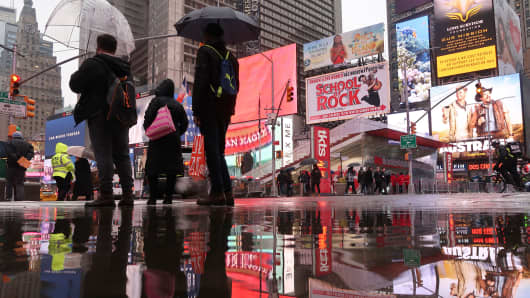 People wait to cross a street in Times Square in the rain in New York City.