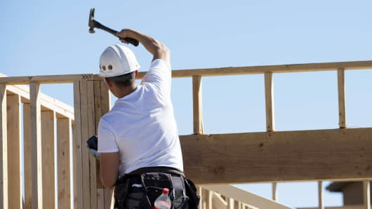 A contractor hammers the frame of a home under construction at the D.R. Horton Express Homes Magma Ranch housing development in Florence, Arizona.